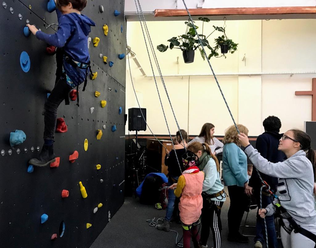 Kinder an einer Kletterwand im Gottesdienstsaal