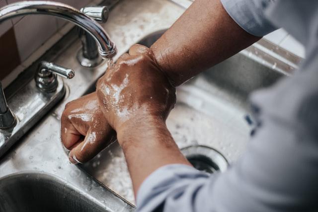 Jemand wäscht sich die Hände unter einem Wasserhahn